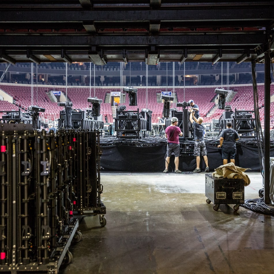 Two employees setting up the stage prior to a concert night.