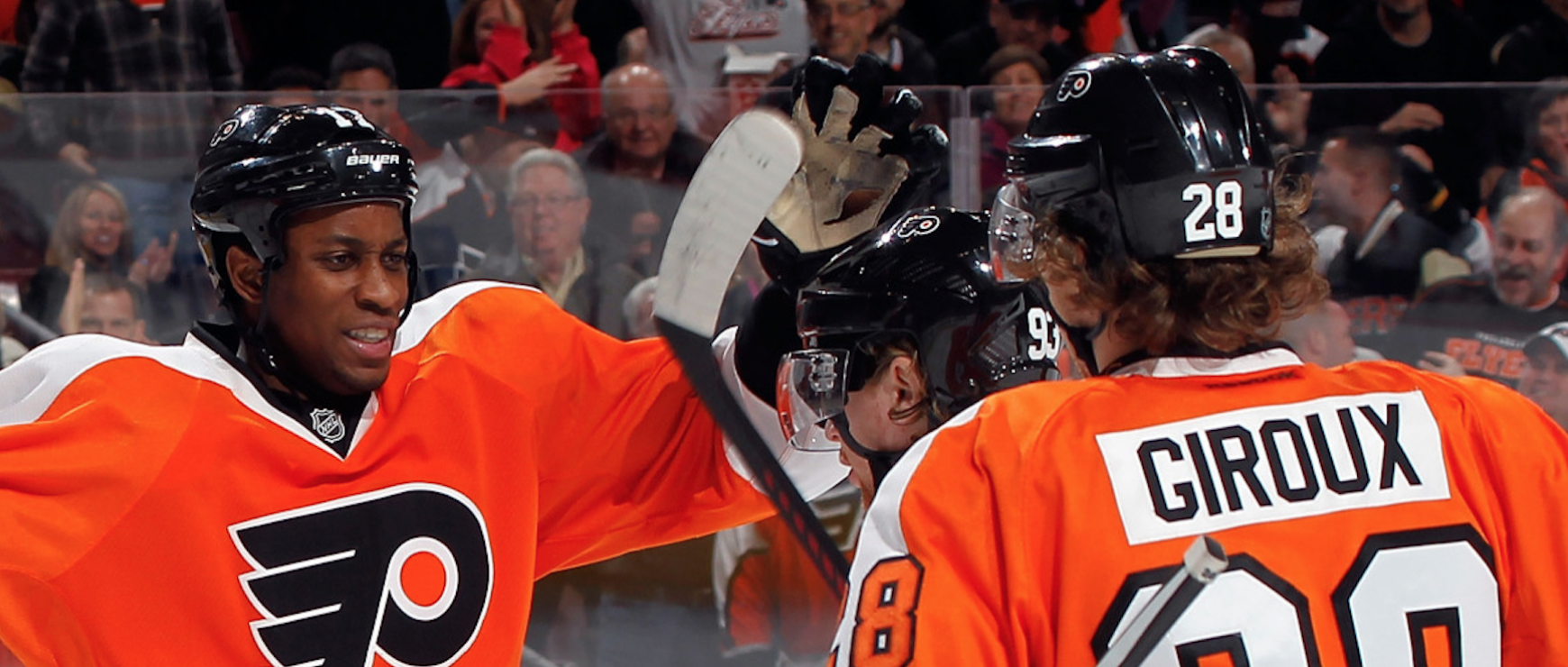 Wayne Simmonds and Claude Giroux celebrating together on the ice during a game night at the Wells Fargo Center