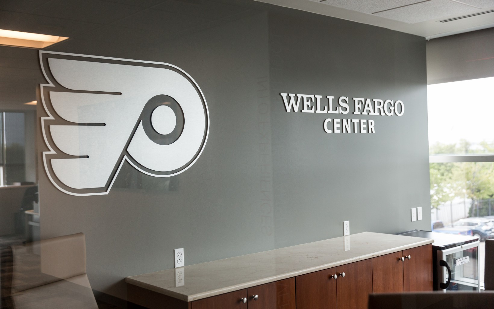 Flyers and Wells Fargo Center logos on the wall of a conference room.