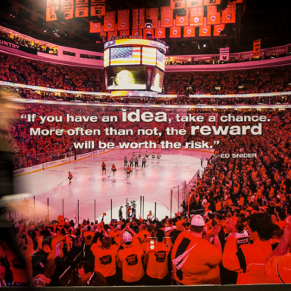 "Employee walking in front of a mural of the Wells Fargo Center bowl packed with fans cheering on the Flyers on a game night. Over the image reads a quote from Ed Snider that says ""If you have an idea, take a chance. More often than not, the reward will be worth the risk."""
