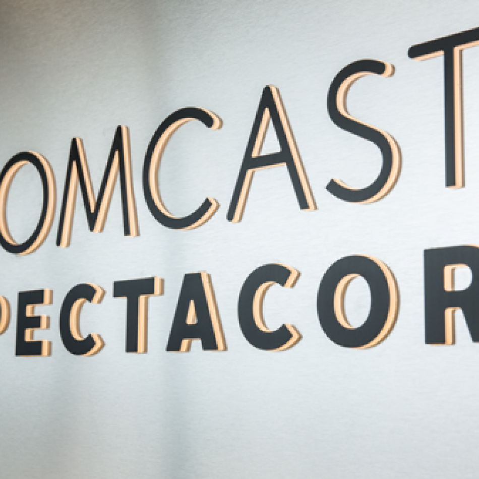 Signage of Comcast Spectacor logo in black on a silver background.