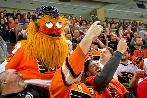 Flyers' mascot Gritty taking selfies with enthusiastic Flyers fans.