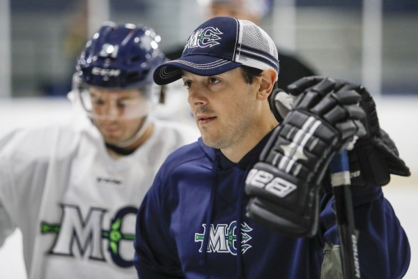 Danny Briere in Maine Mariners gear standing on the ice with Mariners player blurred in the background.